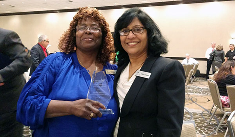 "Charlotte ""Sista C"" Ferrell receiving a University of Phoenix ""Faculty of the Year"" award from Dr. Rada"